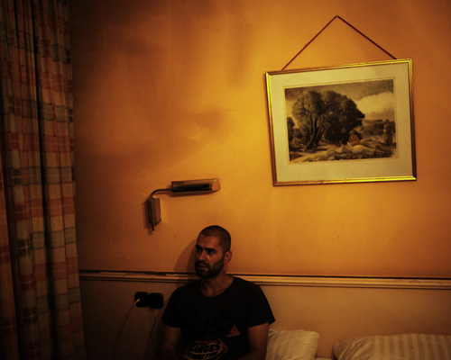 "M. A. Munich, Germany. July 2014 ""If it work, maybe it will be the end of suffering."" M. A. M. A. left Aleppo six month ago, where his parents remain. He is travelling in fear of identity control. In this crappy hotel, the owner don't mind illegal migrant, money is money."""