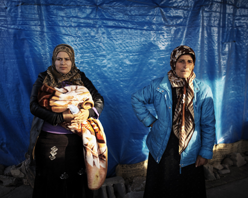 Two Syrians in front of their shelter in an under construction building. Reyhanli, Turkey.