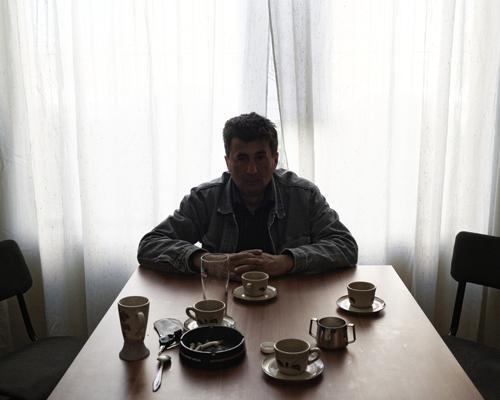 """Un ancien soldat des guerres de Yougoslavie dans les locaux d'une association d'anciens combattants. Zemun, Belgrade.  """"Après cinq ans de guerre, je n'ai pas de pension, ni en Serbie, ni en Croatie... Je ne vais pas te raconter mon histoire, mais celle de mon jumeau, on s'est enrôlés quand on étaient jeunes, on a 47 ans maintenant. Des crimes de guerre ont été commis des deux côtés, les responsables doivent être poursuivis, mais à l'époque nous pensions mener un combat honorable. Mon frère était chauffeur de bus. Jusqu'en 2006, nous avons vécu notre vie.  Un jour, l'insomnie est venue, l'anxiété, ses yeux étaient rouges. Quand notre mère était encore en vie, il est allé chez le médecin, mais il n'a jamais accepté que ce qui lui arrivait. Il a essayé de rester lui même, mais il n'a pas réussi. Il s'est mis à boire beaucoup, il a perdu son boulot, entre temps notre mère est morte, il est devenu plus agressif envers ma femme et moi. Il est resté seul dans une maison qu'il a construite et dévastée, il était violent envers tout et tout le monde. L'isolement total est venu. Puis l'hiver. Je l'ai trouvé nu et affamé. Il a survécu grâce à moi, pas par la grâce de l'État. D'un homme très silencieux, il est devenu tout autre. Aucune institution n'en veut. C'est un paria."""""""