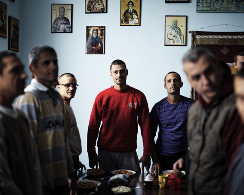 """Prière avant le repas dans une communauté de La terre des vivants, un centre pour toxicomane près de Novi Sad.  Les hommes viennent de différents milieux : de fermier à directeur d'une prestigieuse institution artistique. Les addictions vont de l'alcool à l'héroïne en passant par les jeux. Ils on entre une petite vingtaine et la fin de quarantaine. Certains sont ici depuis un an.  """"La terre des vivants existe depuis 10 ans. Il y a six communautés dont une pour les femmes. C'est sous l'hospice du monastère orthodoxe de Kovilj, c'est un projet de l'église. On collabore avec la municipalité de Novi Sad. C'est entièrement gratuit, non médicalisé. Les gens doivent venir de leur propre chef, ils peuvent aussi partir. Dernièrement les gens prennent plus de speed, de la cocaïne ou de l'ecstasy plutôt que de l'héroïne."""""""