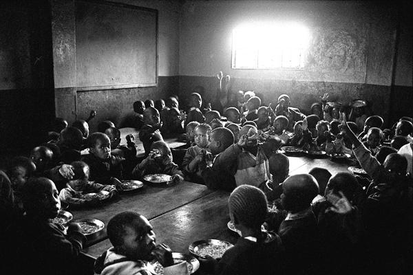 Salle à manger d'une école. Pas de couverts, menu unique.